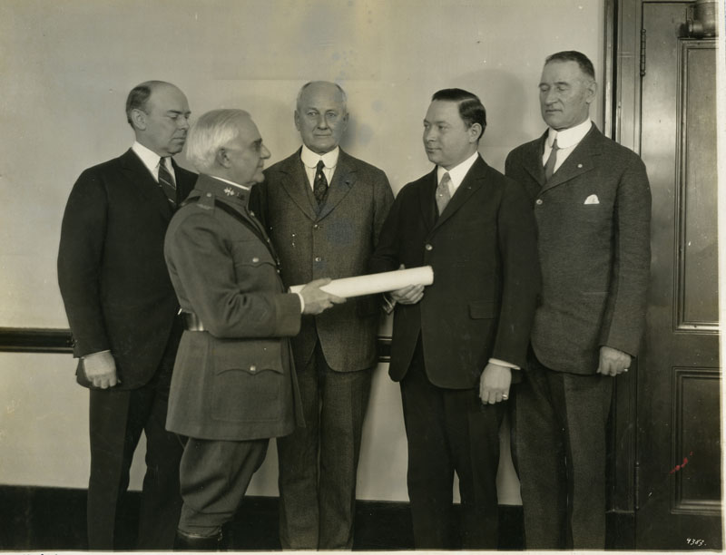 Sarnoff is handed a paper which is his commission into the Army