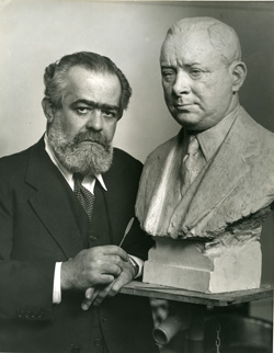Sculptor Jo Davidson poses with his bust of Sarnoff