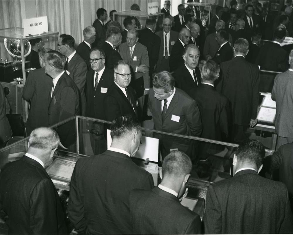 The crowded opening of the Sarnoff library, many guests inspect cases of artifacts