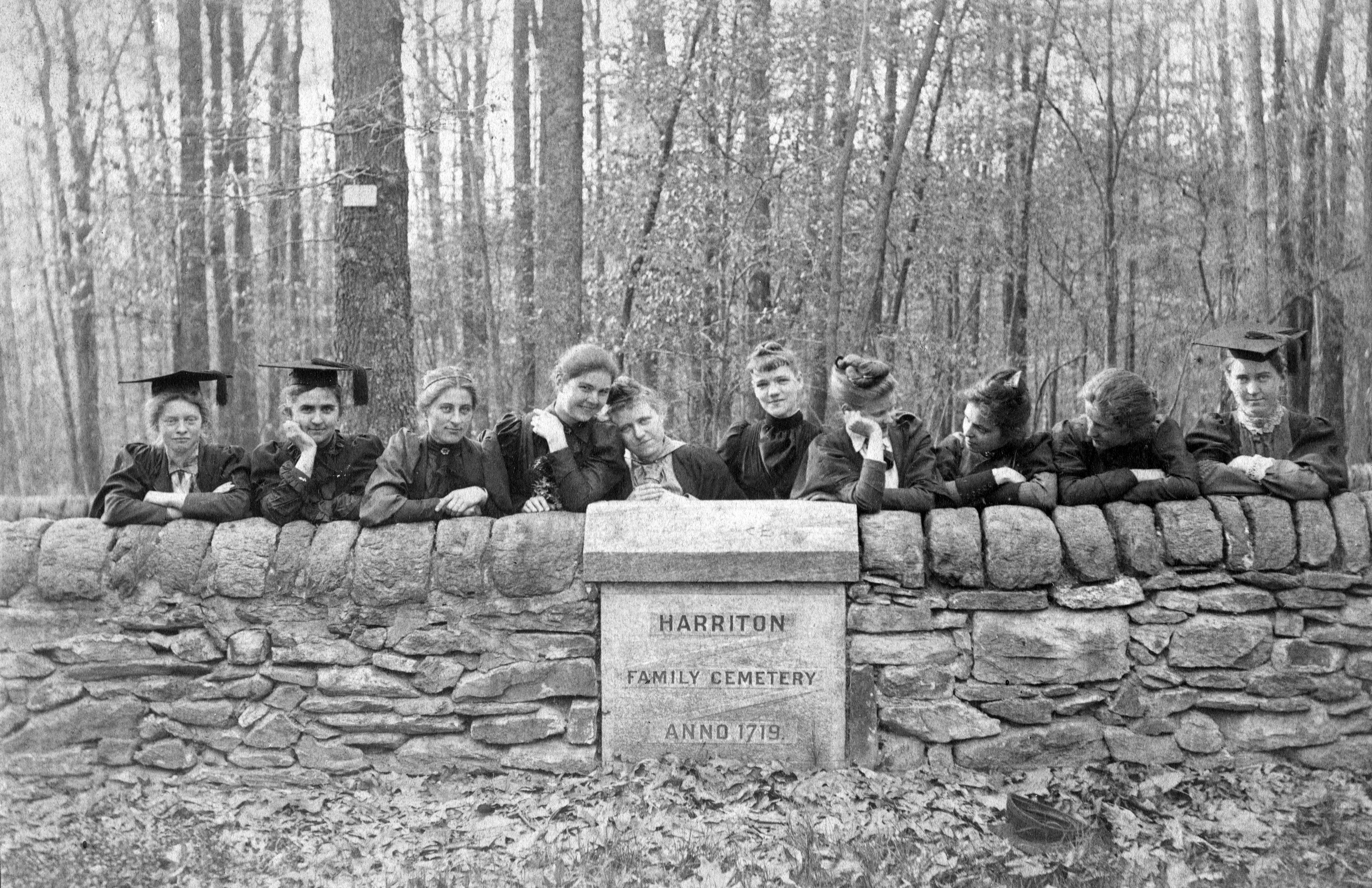 Black and white photo of women posing behind a low wall for a family cemetery plot.