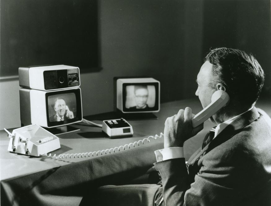 A man talks on the photo while being able to see himself and his meeting partner on small televisions