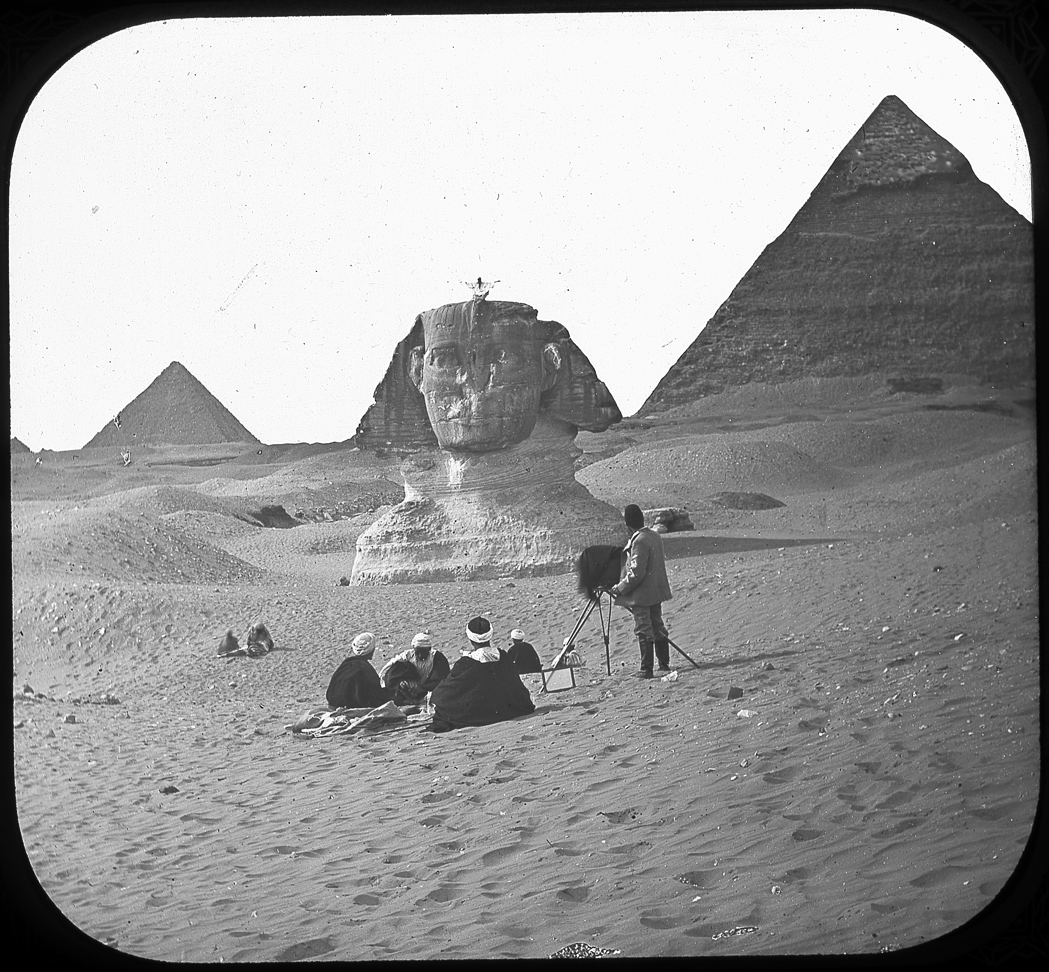 Black and white image of a photographer capturing a person sitting atop the at Sphinx, with the Pyramid of Chephren in the background