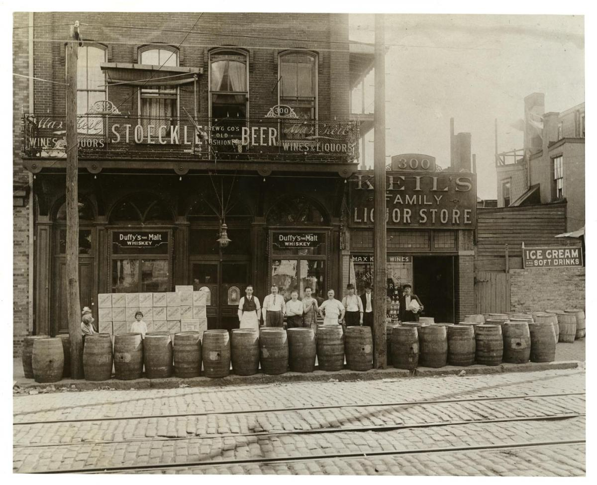 Men stand outside a tavern and liquor store with barrels lining the sidewalk