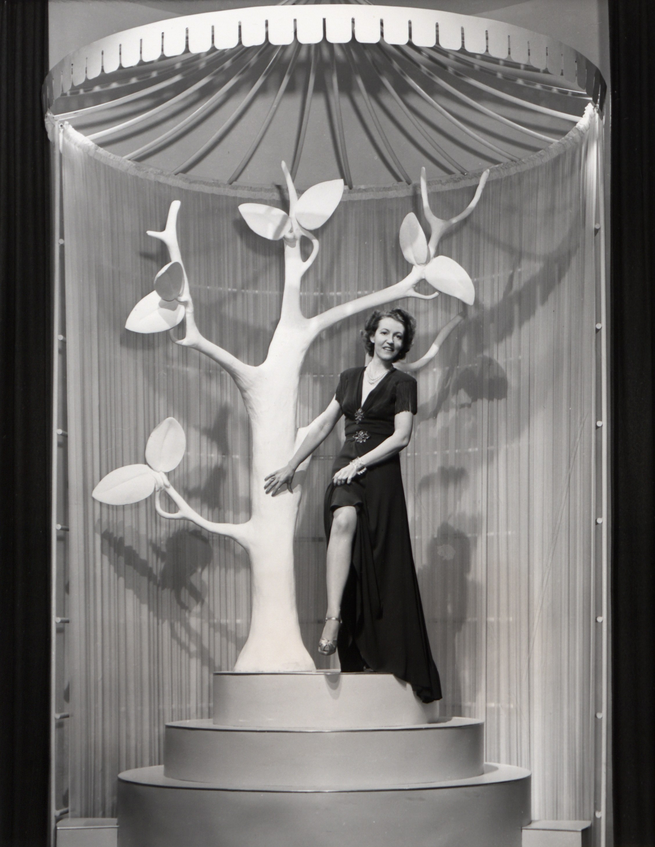 Black and white image of a woman modeling nylon stockings in an exhibit at the New York World's Fair