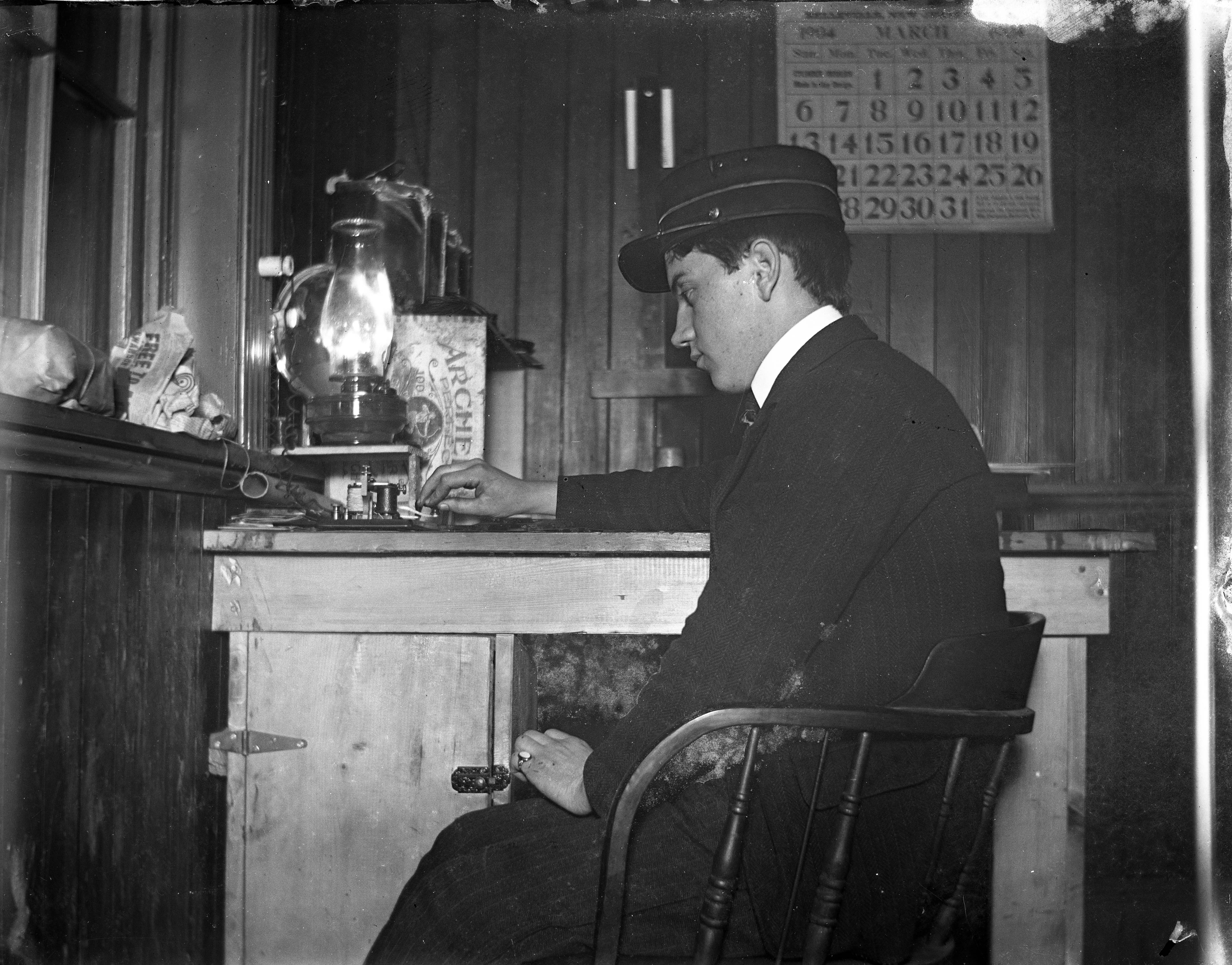 Black and white image of a telegraph operator at work in an office in 1904.