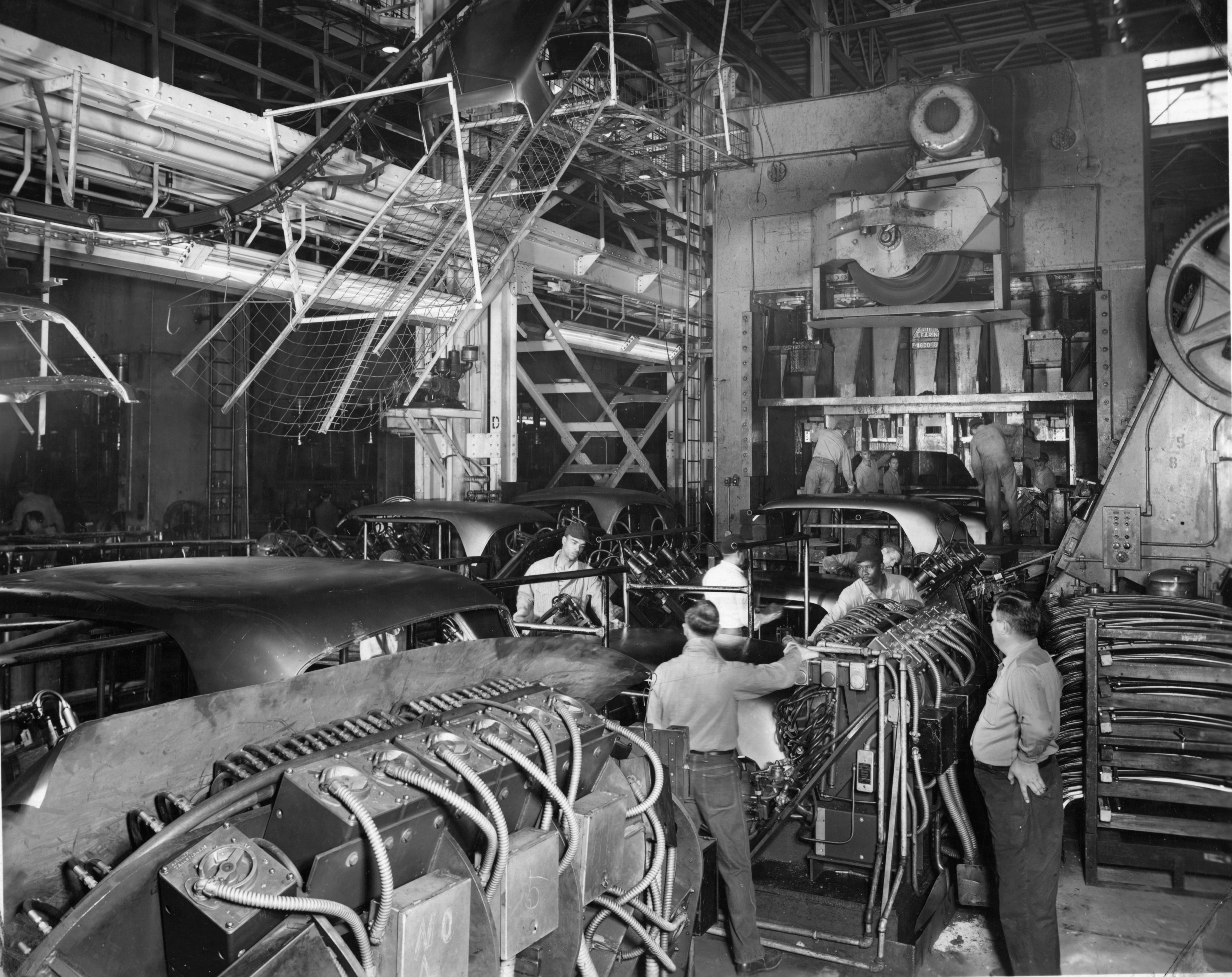 Black and white image of workers assembling automobiles