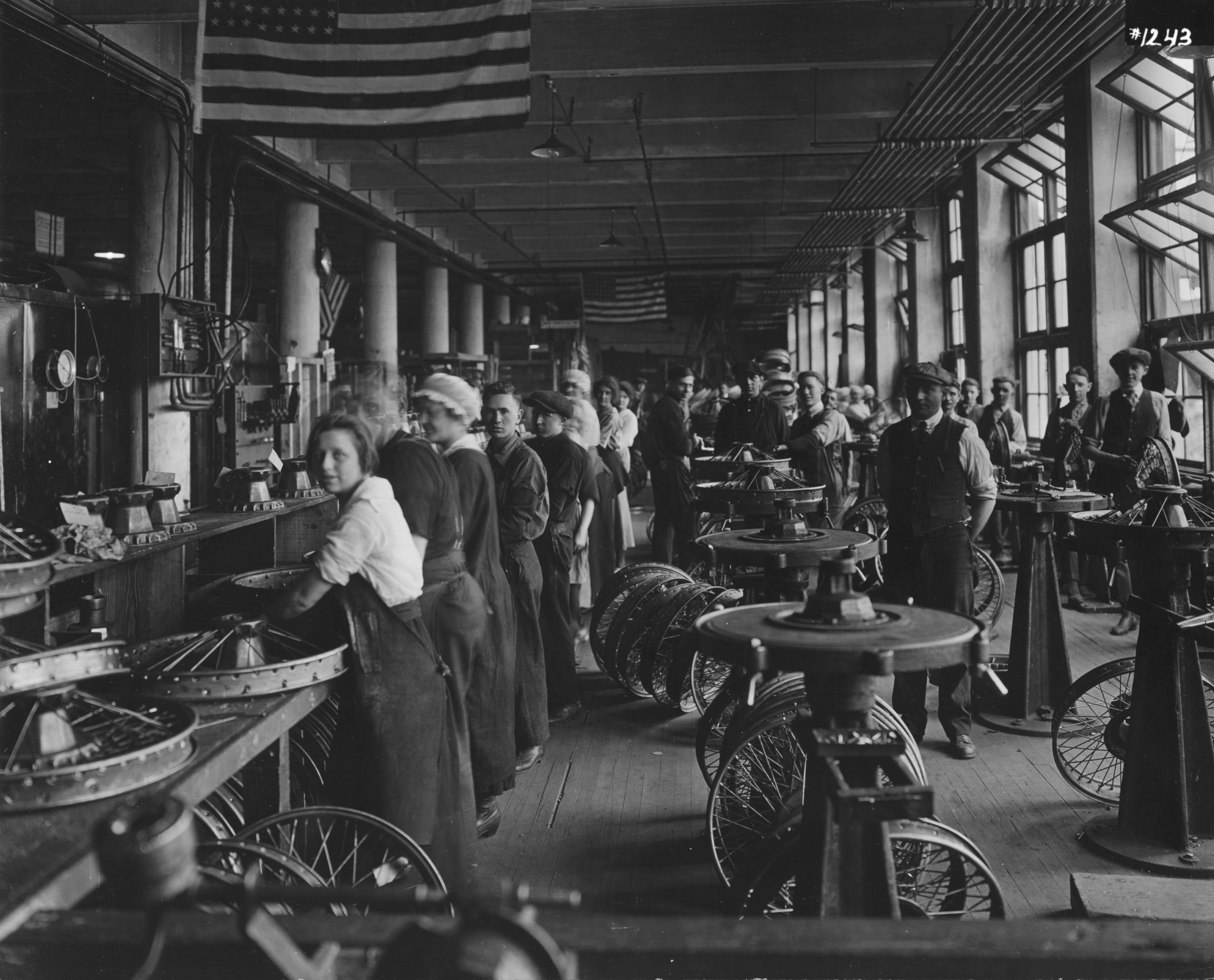 Black and white image of workers on assembly line in wheel factory