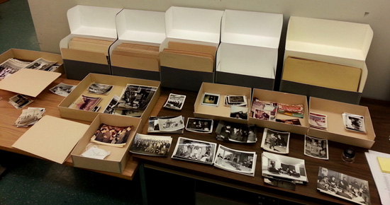 Dozens of photos from the Sarnoff collection laid out on a table for processing