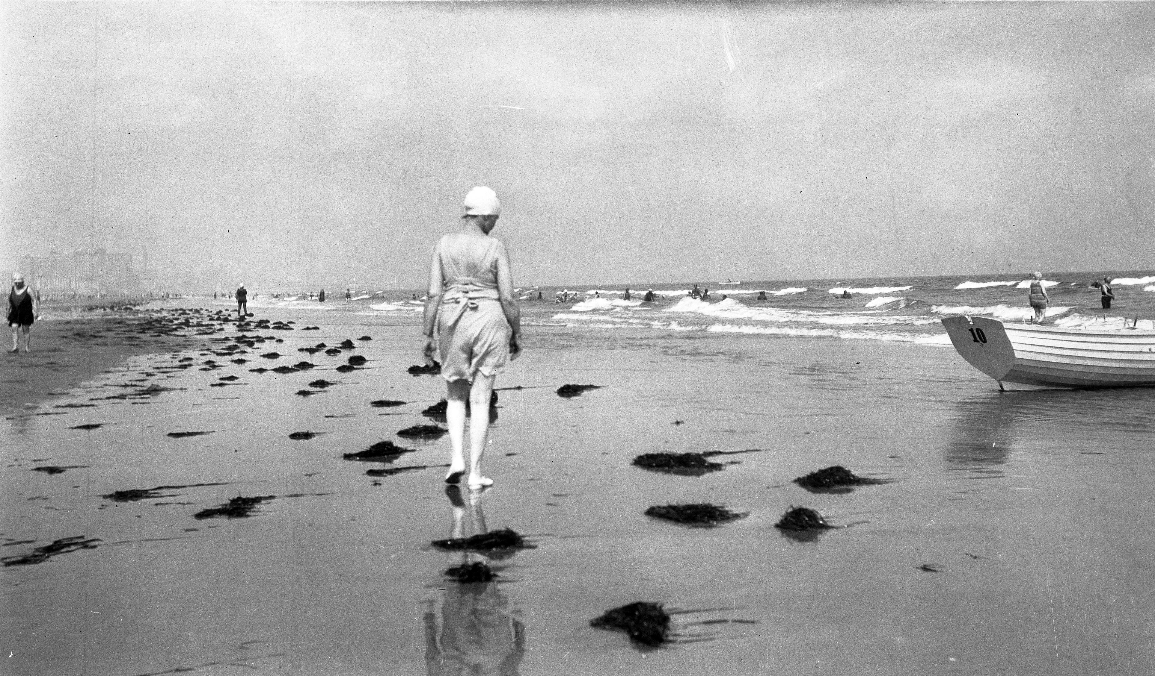 Black and white image of a woman walking on beach with back to camera at Ventnor, New Jersey, or Rehoboth, Delaware