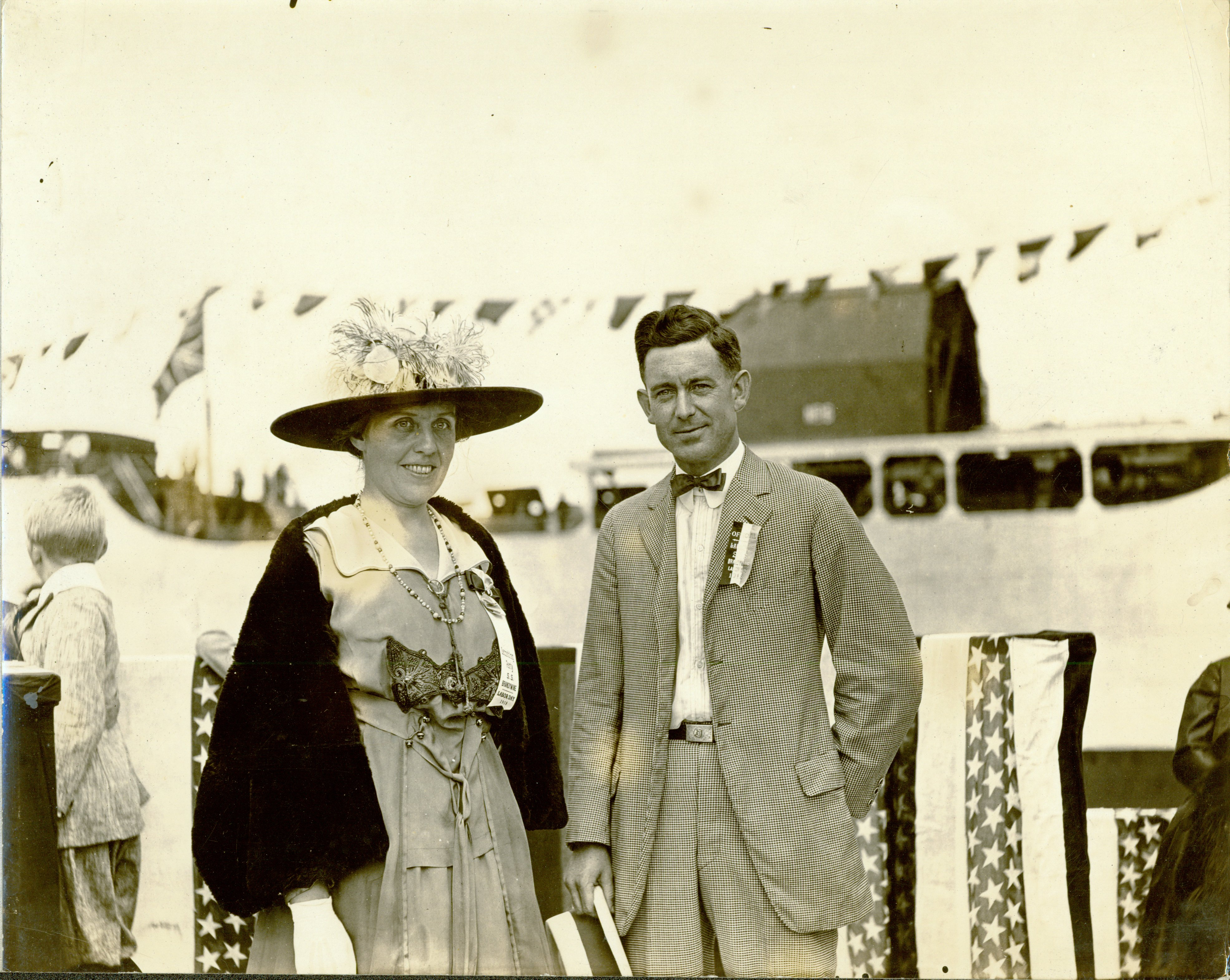 Black and white image of two people attending a ship launching.