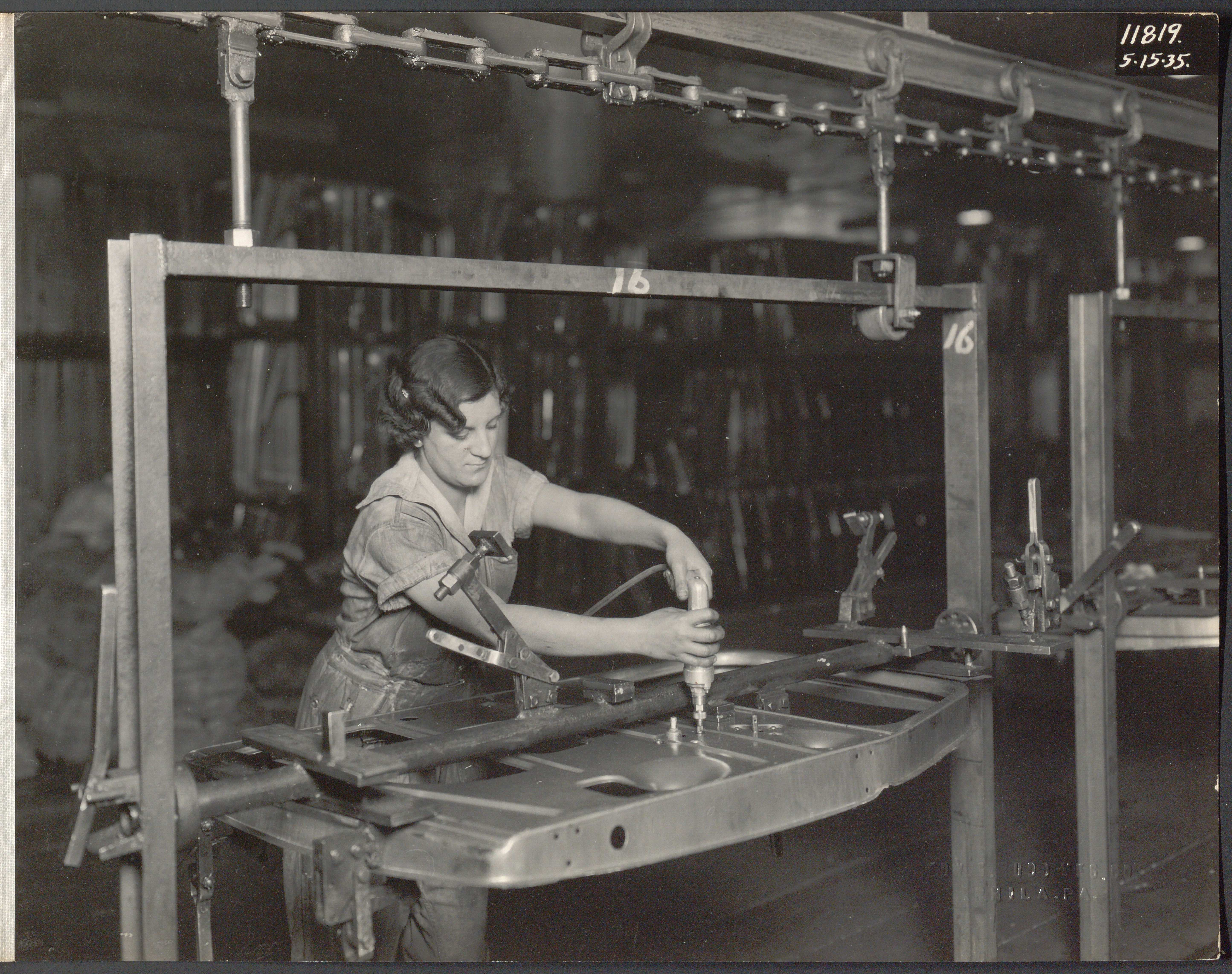 Black and white photograph of a woman in overalls applying fasteners to a metal door panel.