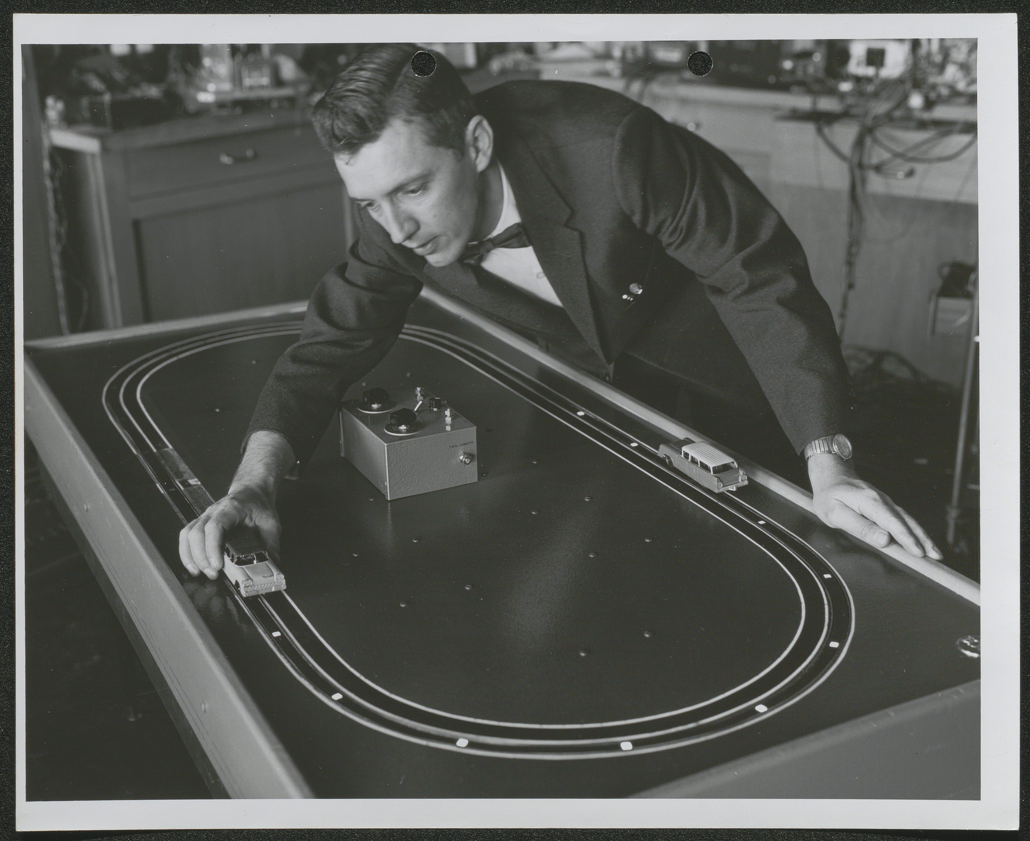 Black and white image of a man moving a model car along an electronic track
