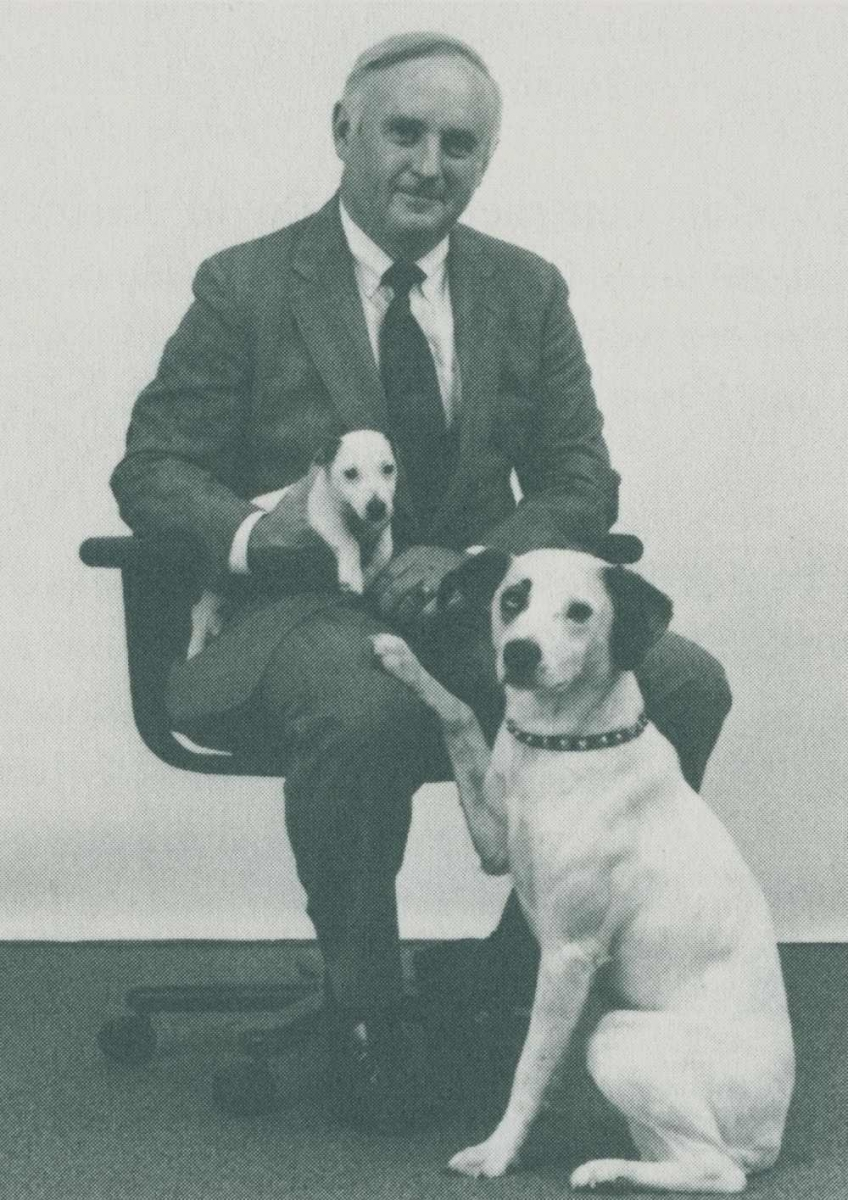 Marty Holleran poses holding the puppy Chipper and next to Nipper the dogo
