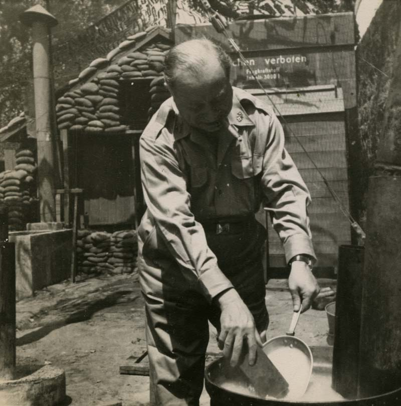 Sarnoff washing his dishes outside