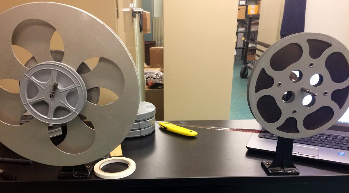 Film on a metal reel, tape and a knife lie on the table