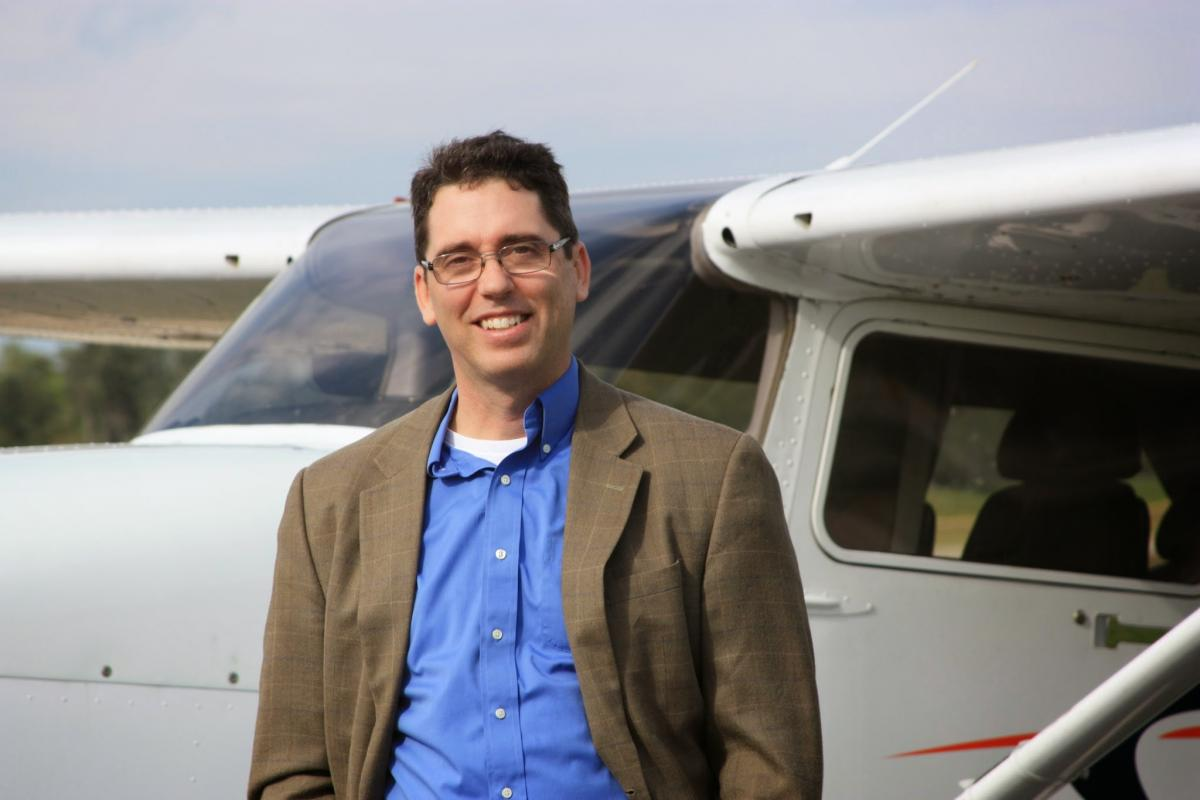 Alan Meyer stands next to a private plane.