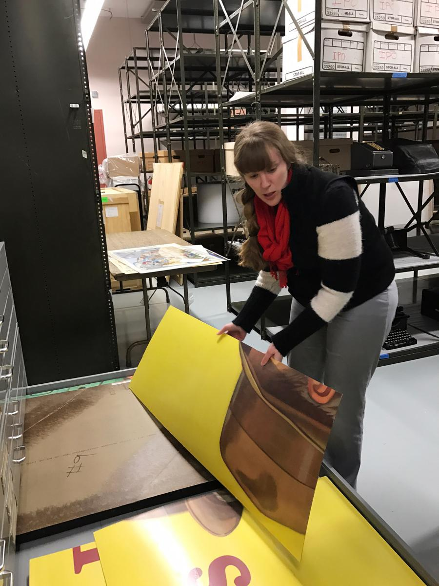 An archivist handles a piece of the large billboard stored in drawers in the archives.