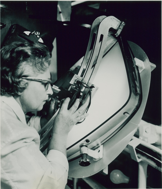 A woman uses a microscope to inspect a tube