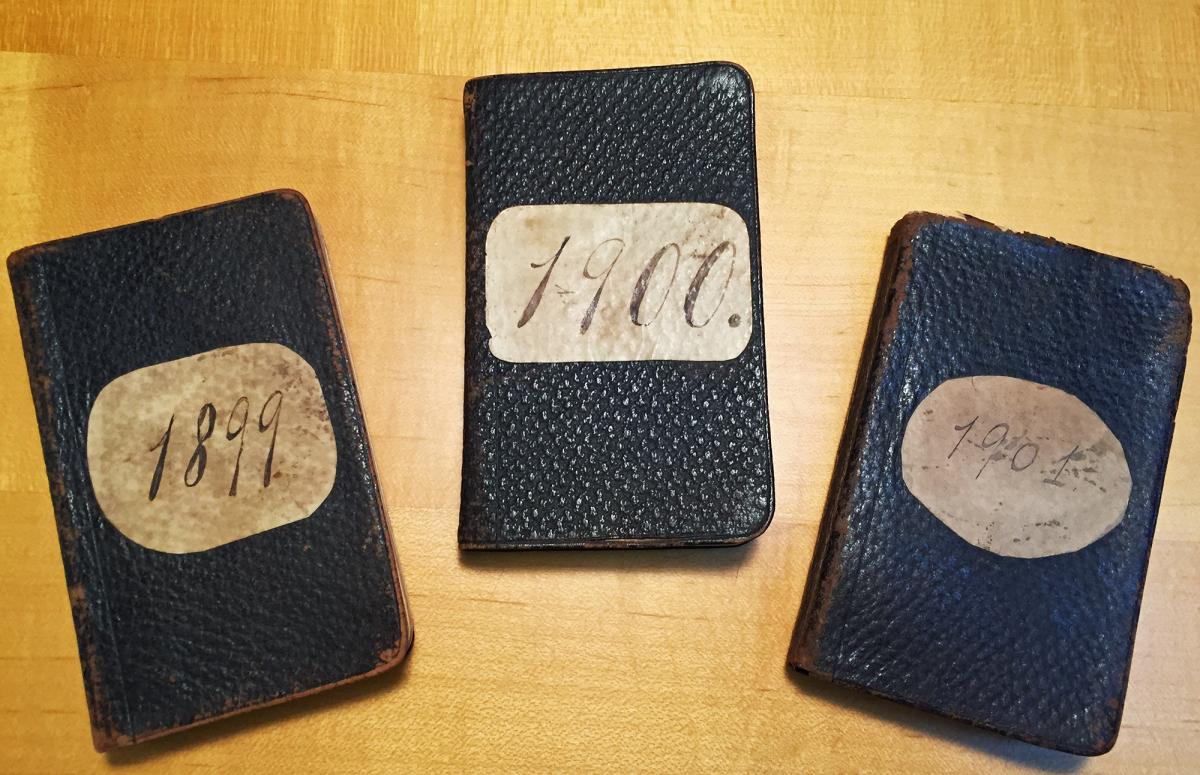 Small black diaries with large oval stickers on front with the years: 1899, 1900, 1901