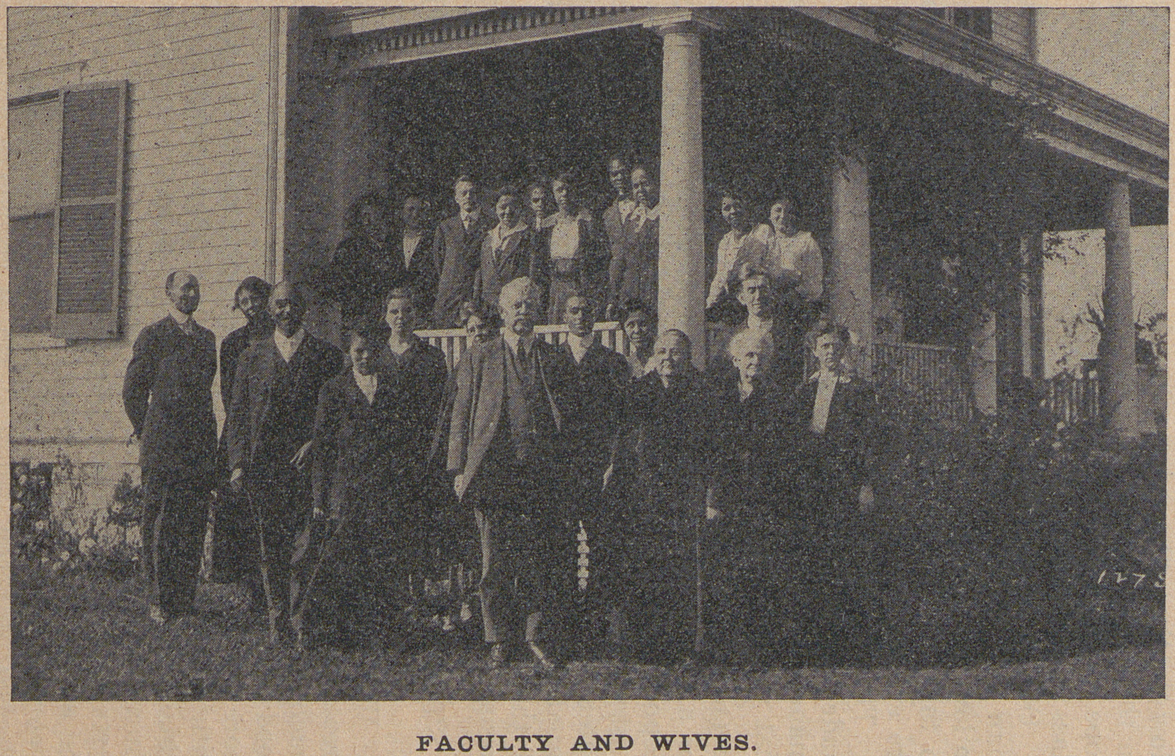 Black and white photograph of an interracial group of educators and their spouses on a porch.