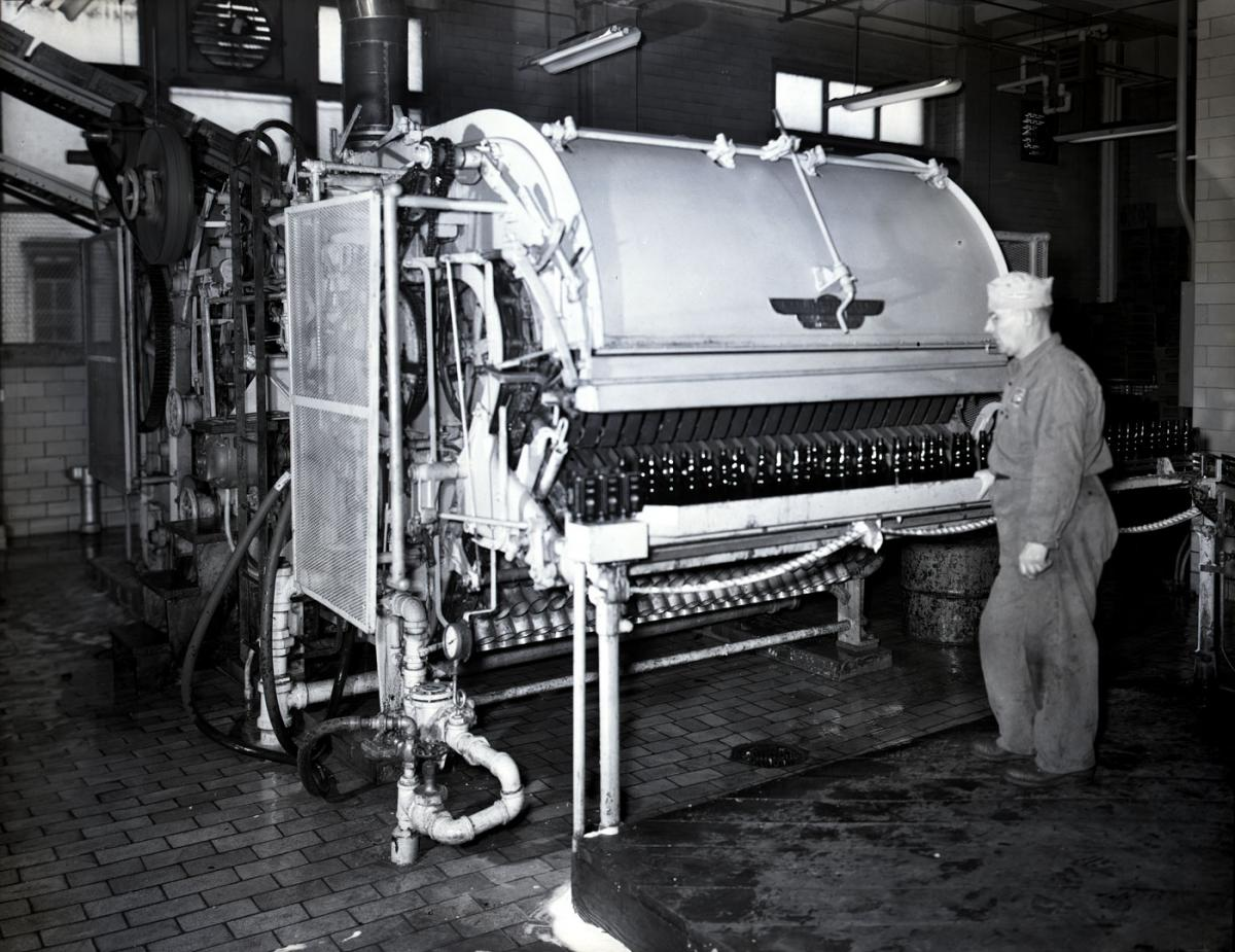 A man stands near a bottling machine