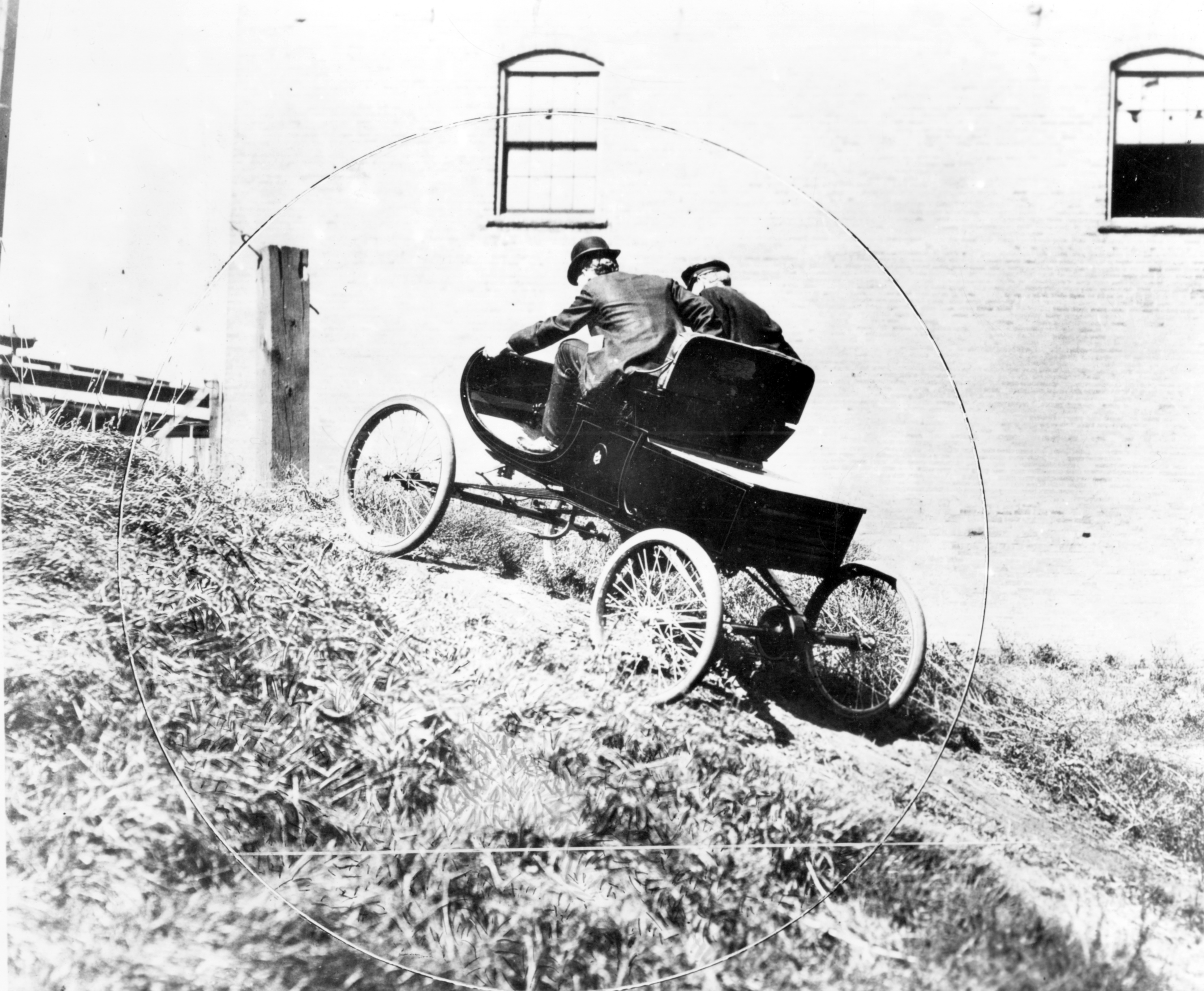 Black and white photograph of two men in a rudimentary automobile driving up a hill.