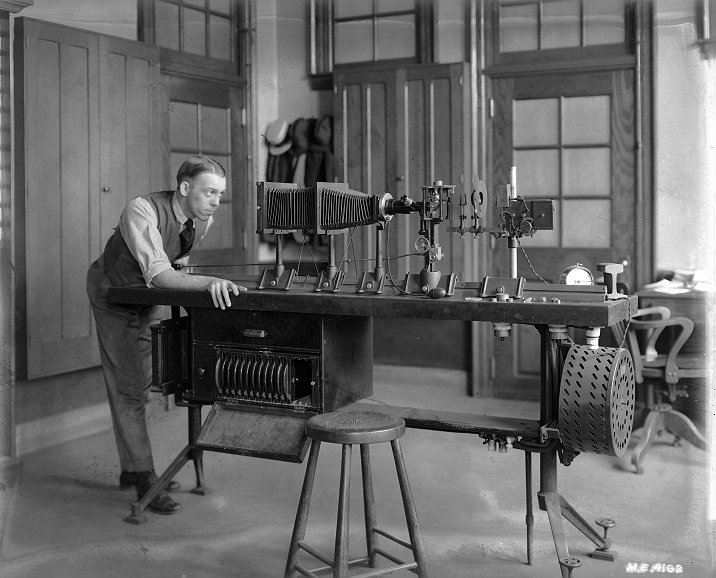 Black and white image of a young man looking into the end of equipment assembled on a tabletop.