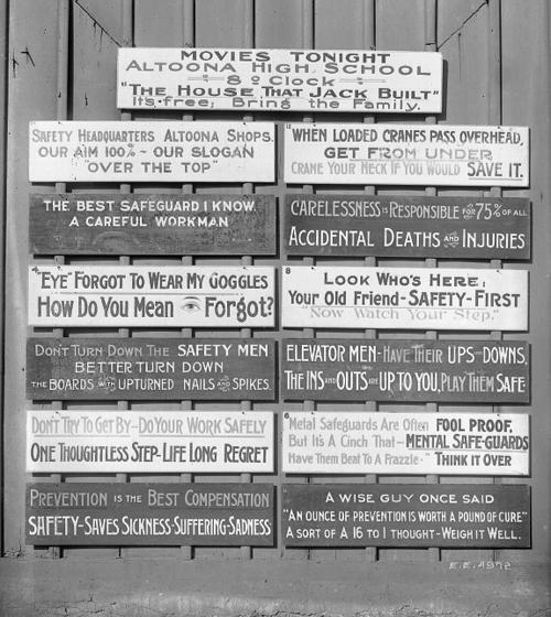 Black and white photo of a collection of signs painted with safety slogans on a wooden wall.