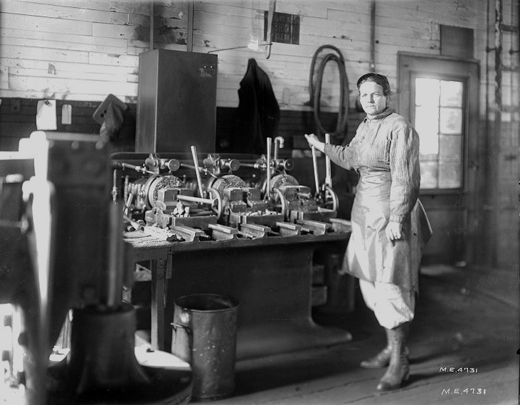 Black and white image of a woman in work clothes standing by a bolt threading machine in a workshop.