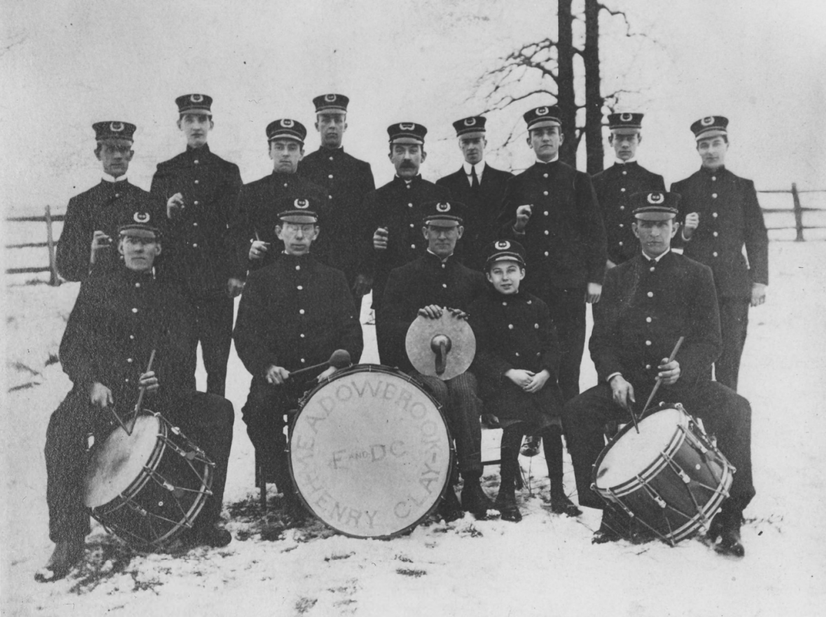 A drum corps poses for a group photo outside in the winter in their band uniforms.