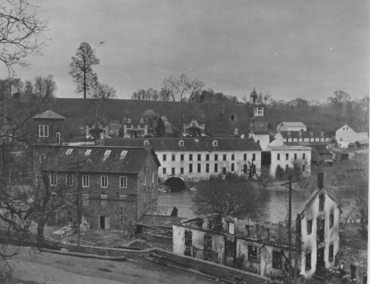 A view of the Brandywine and the mill and buildings that surrounded it. One building is burnt by a fire with no roof.