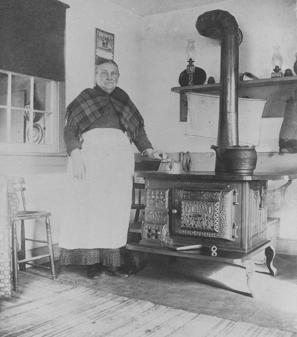 Ellen Maxwell, an older woman, stands at her kitchen stove in the 1800s.