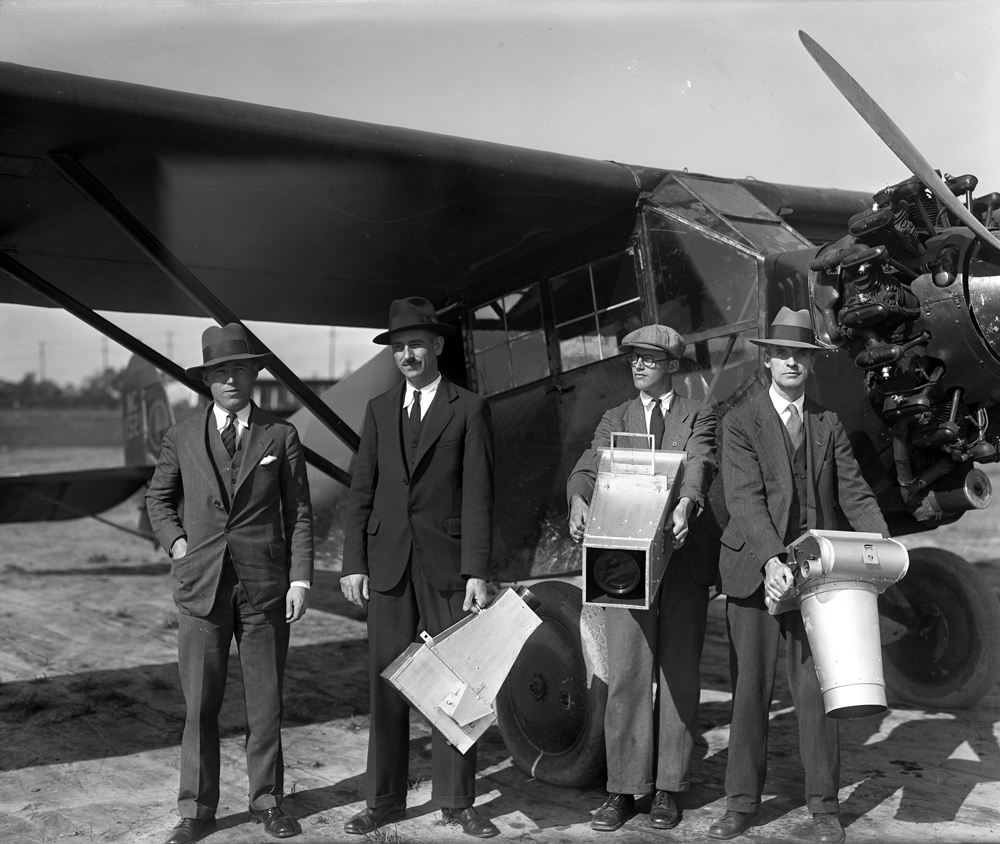 Victor Dallin and his staff with cameras in front of an airplane