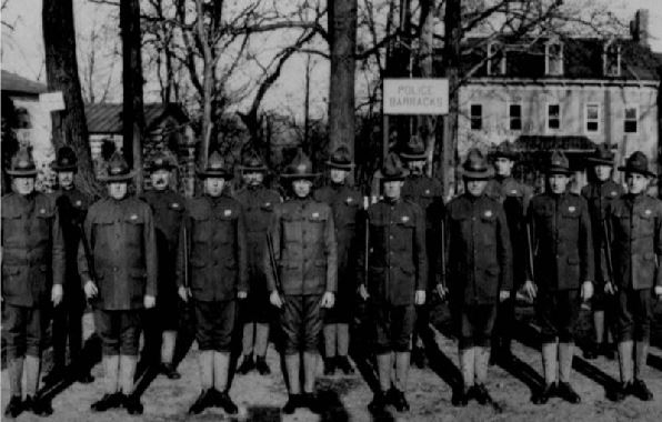 military police in uniform stand in formation in front of their barracks