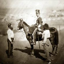 Soldier on his horse, two helpers stand nearby
