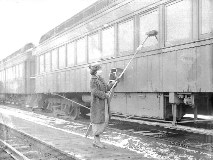Female worker cleans train windows