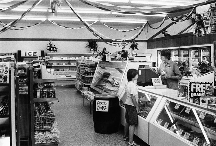 Inside of a wawa food market, a young boy pays at the register