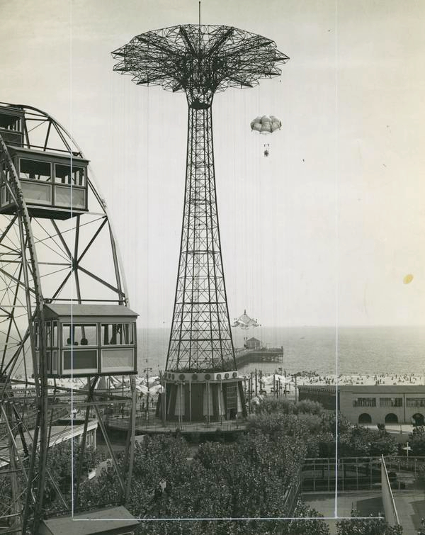 Black and white photograph, taken from a height, of a seaside amusement park. Main feature is the Parachute Jump ride.