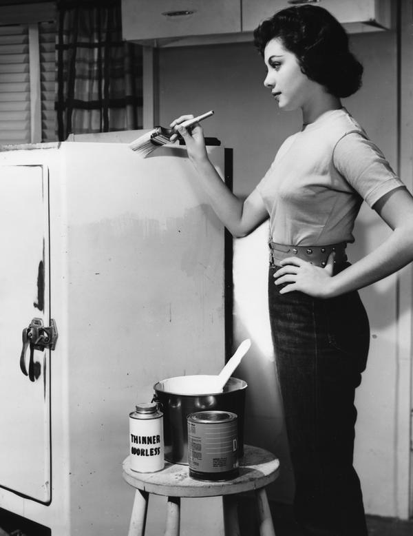 Black and white image of a woman painting a refrigerator