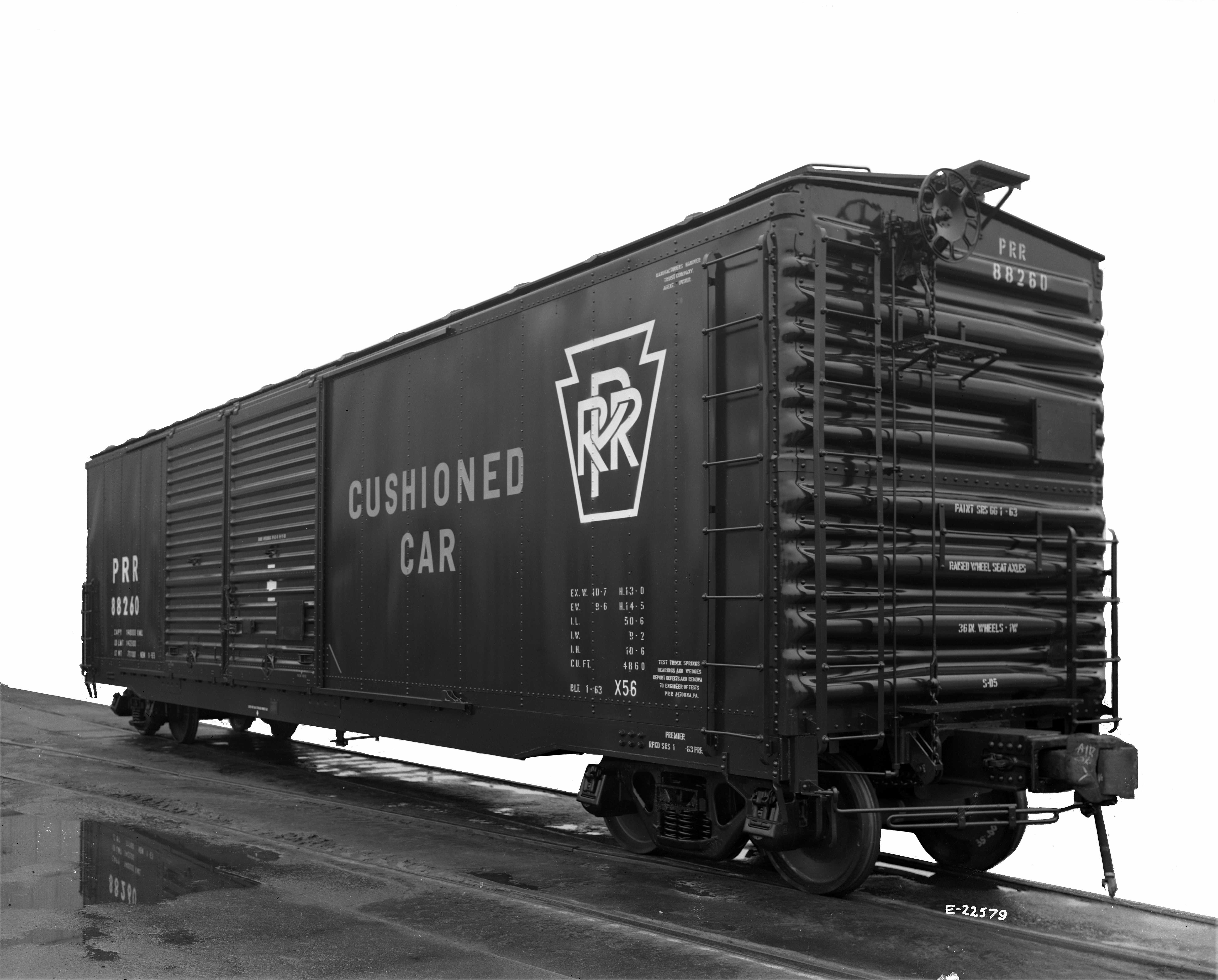 """Black and white, 3/4 view of a railroad box car. Stenciling on side reads """"Cushioned car""""."""