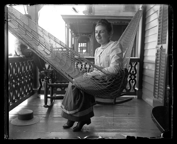 Black and white photograph of a woman in a hammock on a porch