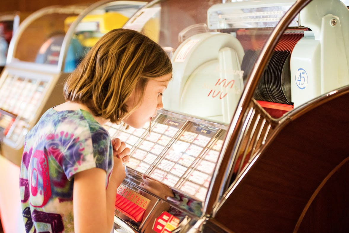 A young girl looks at a vintage jukebox