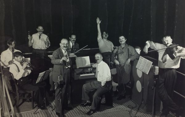 Men wear large false mustaches and play musical instruments