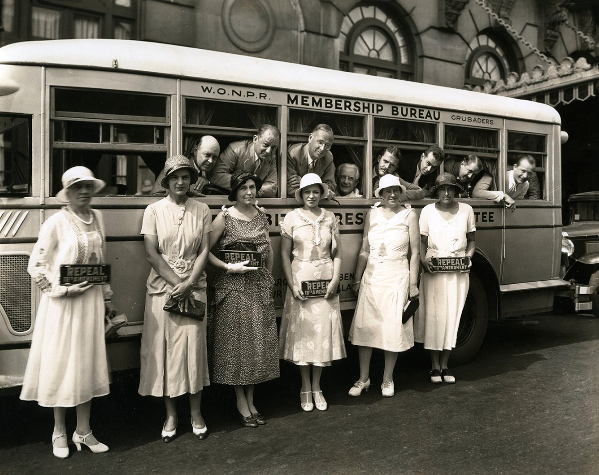 "Women at a prohibition rally with bus and ""repeal"" signs."