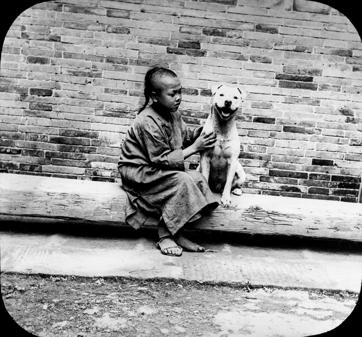 A lantern slide from the Ferracute Machine Company, depicting an unidentified child sitting with Snooks the dog in China, 1898.