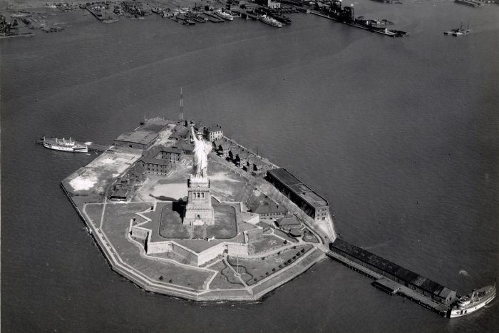An aerial view of the statue of liberty in black and white.