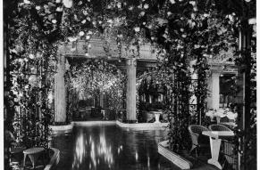 Black and white image of an interior pool surrounded by seating and covered by flowered pergolas