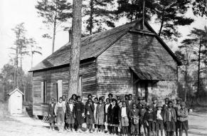 Black and white photo of young, Black schoolchildren outside a one room schoolhouse.