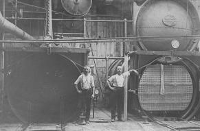 Black and white image of two workers with bleaching machines at Joseph Bancroft & Sons Co. mill