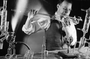 Black and white image of a glass blower making chemical laboratory glassware